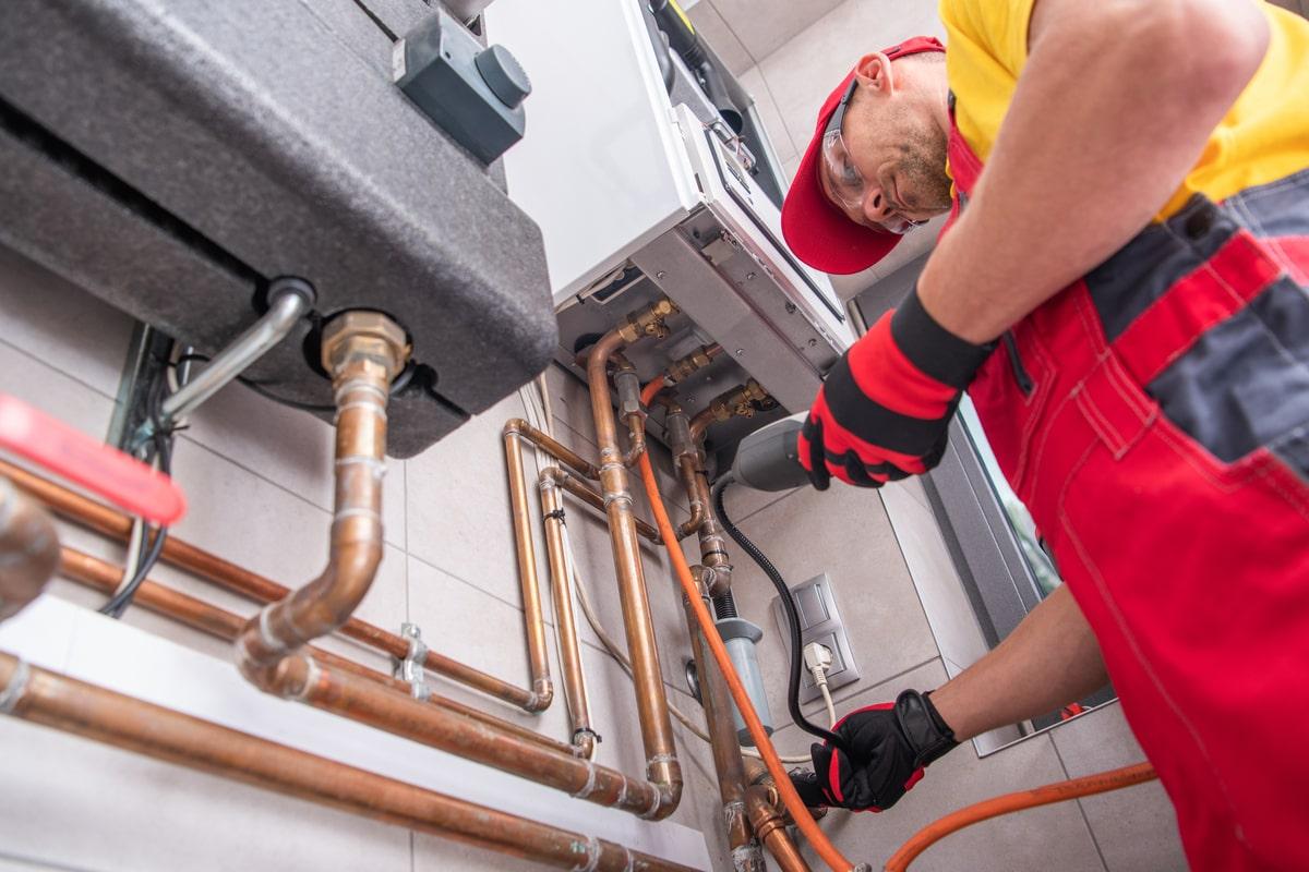 persoana care verifica tevile de apa si de gaz ale unei centrale termice